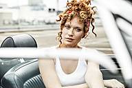 Portrait of redheaded woman in sports car - FMKF04504
