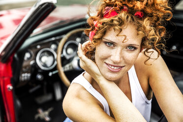 Portrait of smiling redheaded woman in sports car - FMKF04507