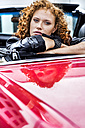 Portrait of confident redheaded woman in sports car - FMKF04519
