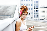 Portrait of redheaded woman holding cell phone - FMKF04522