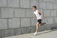 Young man running along wall - VPIF00062