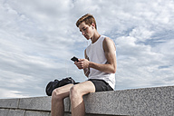 Young athlete sitting on a wall with cell phone and earphones - VPIF00065