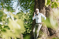 Mature man on cell phone leaning against tree - JOSF01696