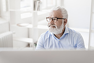 Smiling mature man with beard and glasses at desk - JOSF01702