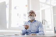 Mature man with beard and glasses working at desk - JOSF01705