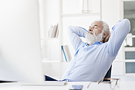 Mature man with beard relaxing at desk - JOSF01708