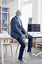 Smiling mature man with beard and glasses sitting on desk - JOSF01717