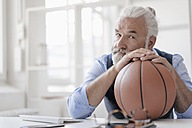 Portrait of mature man on at desk with basketball - JOSF01726