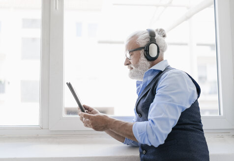 Mature man with tablet and headphones at the window - JOSF01729