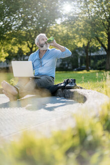 Mature man drinking beer and using laptop in park - JOSF01738