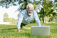 Mature man with laptop exercising in park - JOSF01741