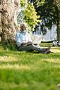 Mature man using laptop in park - JOSF01744