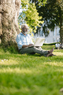 Mature man using laptop in park - JOSF01744