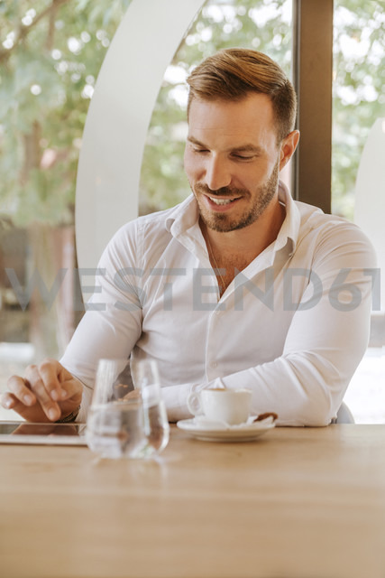 Smiling man with tablet in a cafe - ZEDF00846