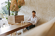 Smiling man with tablet in a cafe - ZEDF00849