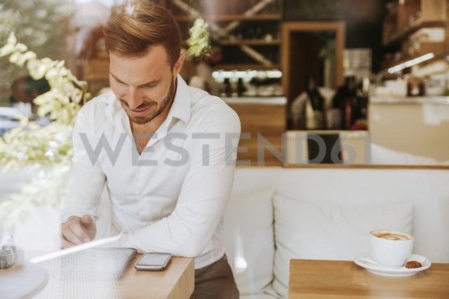 Smiling man with tablet and cell phone in a cafe - ZEDF00864