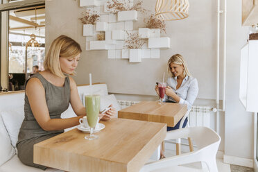Two young women using smartphones in a cafe - ZEDF00867