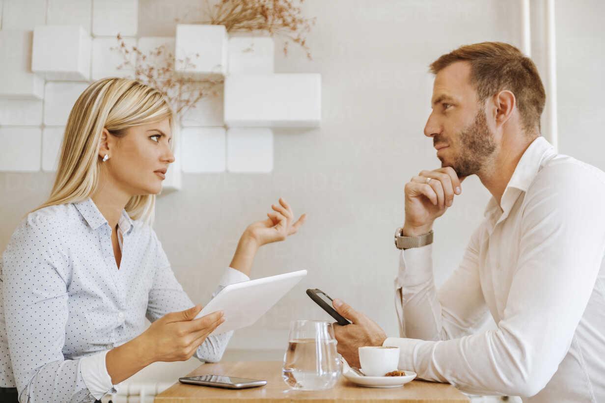 Businessman and businesswoman having a meeting in a cafe - ZEDF00870 - Zeljko Dangubic/Westend61