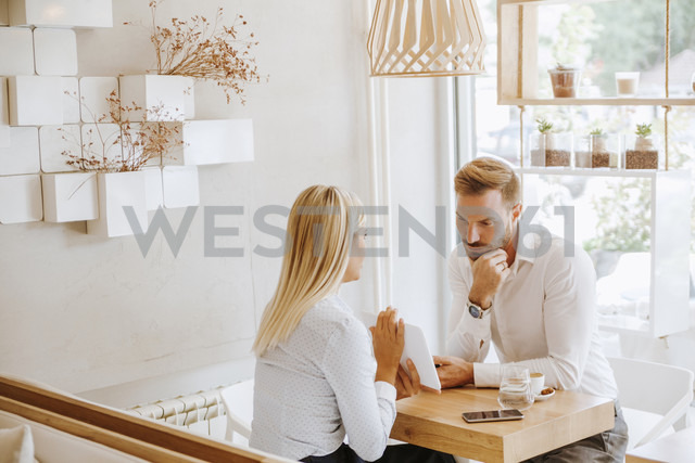 Businessman and businesswoman having a meeting in a cafe - ZEDF00873