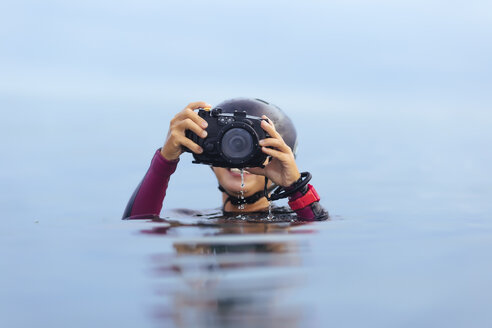 Smiling woman holding underwater camera in the ocean - KNTF00898
