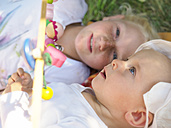 Amazed baby girl lying with her sister on blanket on a meadow - LAF01888