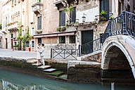 Italy, Venice, bridal couple standing face to face on stairs near canal - DIGF02849