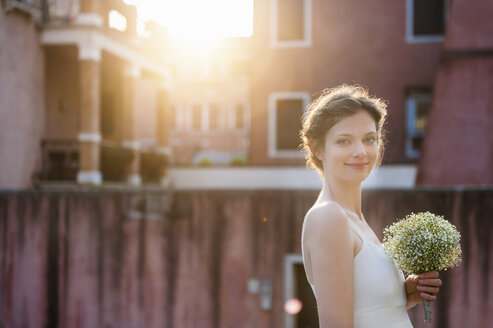 Italy, Venice, portrait of smiling bride with bridal bouquet at sunrise - DIGF02855