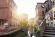 Italy, Venice, kissing bridal couple standing on stairs at sunrise - DIGF02858
