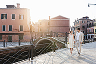 Italy, Venice, bridal couple walking hand in hand at sunrise - DIGF02861