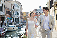 Italy, Venice, happy bridal couple walking hand in hand at morning twilight - DIGF02867