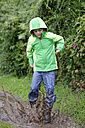 Boy wearing hooded anorak jumping into a muddy puddle - LBF01640