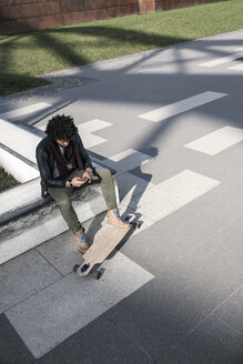 Man sitting in skatepark with longboard typing on smartphone - SBOF00667