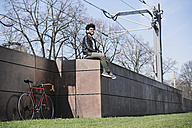 Smiling man sitting on a wall listening to music - SBOF00670