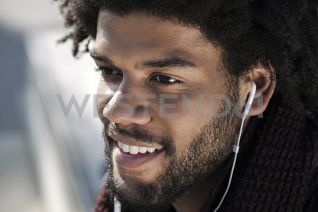 Portrait of smiling man listening to music on his earphones - SBOF00676 - Steve Brookland/Westend61