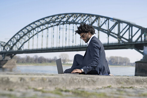 Businessman sitting at the riverside using laptop - SBOF00679
