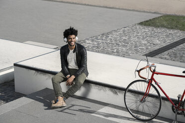 Smiling man listening to music on headphones next to his bicycle - SBOF00691