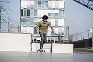Young man riding longboard in skatepark - SBOF00694