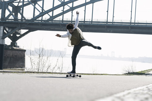 Young man balancing on longboard at the riverside - SBOF00697