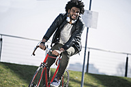 Smiling man riding bicycle - SBOF00700