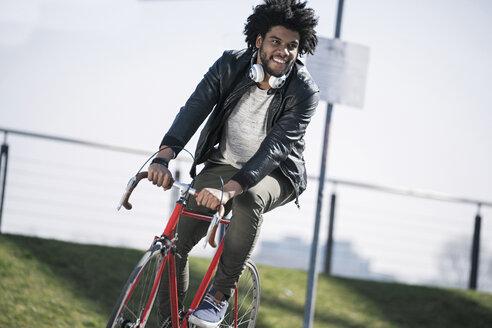 Smiling man riding bicycle - SBOF00700