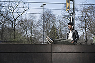 Smiling man sitting on wall listening to music next to  train rails - SBOF00703