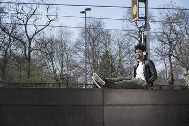 Smiling man sitting on wall listening to music next to  train rails - SBOF00703
