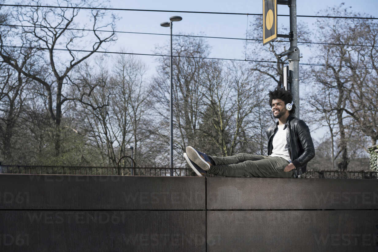 Smiling man sitting on wall listening to music next to  train rails - SBOF00703 - Steve Brookland/Westend61