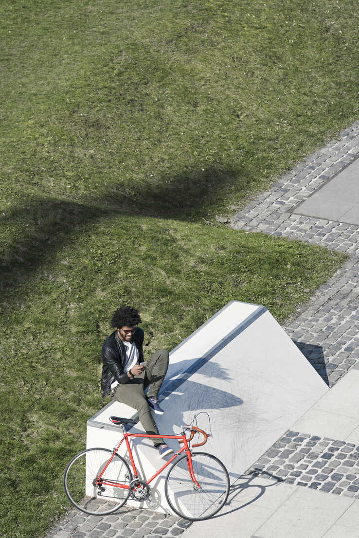 Man sitting in city skatepark with smartphone next to his bicycle - SBOF00709 - Steve Brookland/Westend61