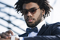 Serious young man with sunglasses looking at his smartwatch - SBOF00718