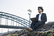 Businessman sitting at the riverside using laptop - SBOF00721