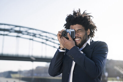 Smiling man in suit at the riverside taking a picture with a vintage camera - SBOF00724