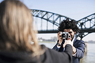 Smiling man in suit at the riverside taking a picture of his girlfriend with a vintage camera - SBOF00727
