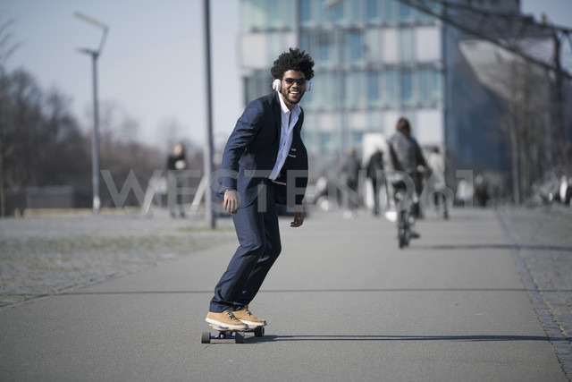 Smiling businessman riding longboard in front of skyscraper - SBOF00730 - Steve Brookland/Westend61