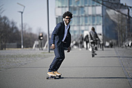 Smiling businessman riding longboard in front of skyscraper - SBOF00730